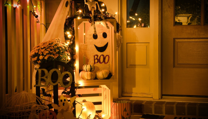 Front of a house covered in Halloween decorations such as pumpkins, ghost buckets and fairy lights