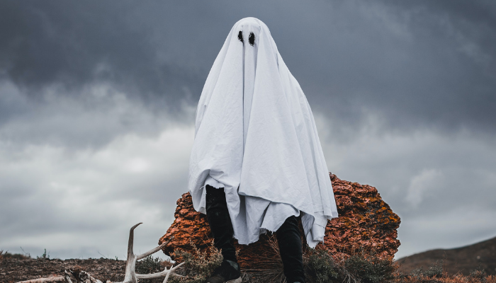 Boy with sheet over pretening to be a ghost in the moors
